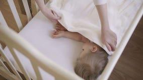 El bebé 2 años que dormían en un pesebre cubrió la manta blanca La mamá cubre al bebé con una manta Sueño diurno almacen de video