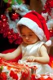 El bebé abre su primer regalo de la Navidad imágenes de archivo libres de regalías