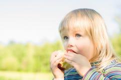 El bebé adorable come la manzana roja en parque foto de archivo