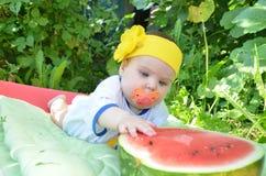 El bebé adorable lindo de los ojos azules 6 meses saca mitad de una sandía en el fondo del follaje Día asoleado Foto de archivo