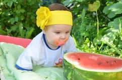 El bebé adorable lindo de los ojos azules 6 meses saca mitad de una sandía en el fondo del follaje Día asoleado Imágenes de archivo libres de regalías