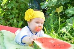 El bebé adorable lindo de los ojos azules 6 meses saca mitad de una sandía en el fondo del follaje Día asoleado Imagenes de archivo