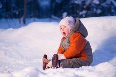 El bebé adorable lindo se sienta en nieve en parque Fotografía de archivo