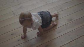 El bebé adorable se arrastra en el piso de la casa Ni?o que juega en casa Niño feliz adorable dentro C?mara lenta almacen de video