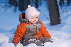 El bebé adorable se sienta en nieve en el parque que mira adelante Foto de archivo