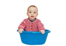 El bebé adorable se sienta en un lavabo azul Imagen de archivo
