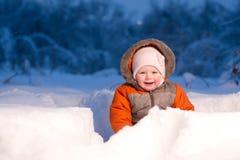 El bebé adorable se sienta y agujero de excavación de la guarida en nieve Imagen de archivo