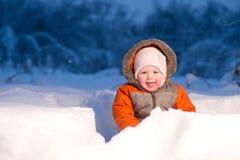 El bebé adorable se sienta y guarida de excavación en nieve Imágenes de archivo libres de regalías