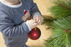 El bebé adorna el árbol de Navidad con la bola roja Fotos de archivo