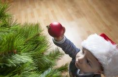 El bebé adorna el árbol de Navidad con la bola roja Imagen de archivo libre de regalías