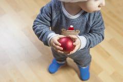El bebé adorna el árbol de Navidad con la bola roja Fotos de archivo libres de regalías