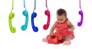 El bebé africano adorable en rojo con un teléfono del vintage y muchos colorean Fotos de archivo libres de regalías