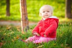 El bebé alegre adorable se sienta en parque en hierba Foto de archivo