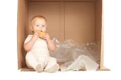El bebé alegre se sienta en rectángulo y come la galleta Imagen de archivo libre de regalías