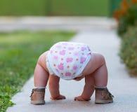 El bebé apenas está jugando en la calle fotos de archivo