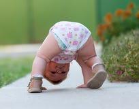 El bebé apenas está jugando en la calle imagen de archivo