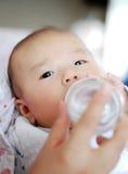 El bebé asiático es leche de consumo imagen de archivo
