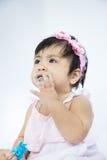 El bebé asiático está comiendo el caramelo y limpia su foc selectivo de la cara sucia Imágenes de archivo libres de regalías