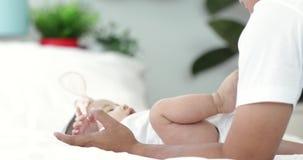 El bebé asiático feliz de la familia con el padre se ríe en casa con la cara de la sonrisa almacen de video