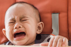 El bebé asiático que se sienta en highchair y que llora rechaza comer f Fotografía de archivo libre de regalías