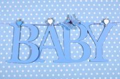 El BEBÉ azul del cuarto de niños del bebé pone letras a la ejecución del empavesado de clavijas en una línea contra un fondo azul Imágenes de archivo libres de regalías