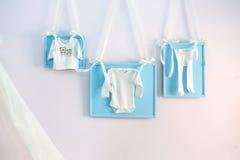 El bebé azul viste en las cintas de la cuerda para tender la ropa en la pared Fotos de archivo