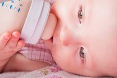 El bebé bebe la leche de una pequeña botella Fotos de archivo