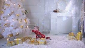 El bebé cerca de un árbol de navidad con un regalo explora presentes y el árbol del Año Nuevo metrajes