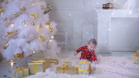 El bebé cerca de un árbol de navidad con un regalo explora presentes y el árbol del Año Nuevo almacen de metraje de vídeo