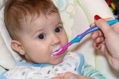 El bebé come la comida sólida por primera vez fotos de archivo
