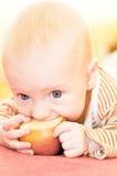 El bebé come la manzana Foto de archivo
