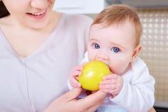 El bebé come la manzana amarilla Niño Imágenes de archivo libres de regalías