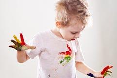El bebé con aguazo manchó las manos y la camisa aisladas Foto de archivo libre de regalías