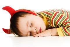 El bebé con el imp de los cuernos duerme en el piso Imágenes de archivo libres de regalías