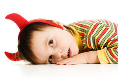 El bebé con el imp de los cuernos duerme en el piso Foto de archivo libre de regalías