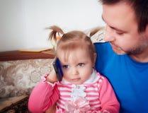 El bebé con el papá consigue llamadas en abuelos Imágenes de archivo libres de regalías