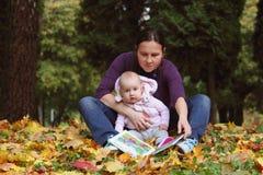 El bebé con la madre leyó el libro Imagen de archivo libre de regalías