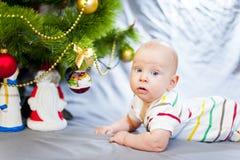 El bebé con los ojos azules acerca al árbol de navidad Año Nuevo Foto de archivo