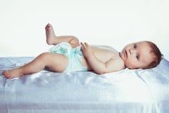 El bebé con los ojos azules miente en colores fotos de archivo