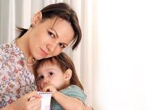El bebé con su mama bebió de una taza imágenes de archivo libres de regalías