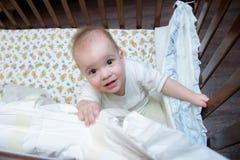 El bebé consiste en el pesebre y la mirada para arriba Imagen de archivo