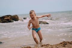 El bebé corre hacia fuera risa de las emociones de la playa del agua imágenes de archivo libres de regalías