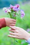 El bebé da a mamá un ramo de wildflowers Imagenes de archivo