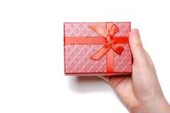 El bebé da sostener una caja de regalo roja aislada en un fondo blanco Visión superior Imagen de archivo