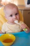 El bebé de 7-8 meses come las patatas trituradas Imagen de archivo