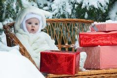 El bebé de la Navidad con el regalo encendido vinewoven el banco Fotos de archivo
