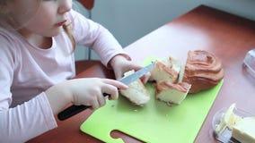 El bebé de la niña mancha la mantequilla en una barra de pan almacen de metraje de vídeo