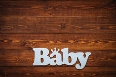 El bebé de la palabra en la tabla de madera marrón Imagenes de archivo