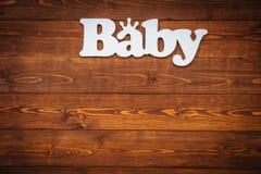 El bebé de la palabra en la tabla de madera marrón Fotos de archivo