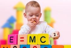 El bebé del genio con el alto índice de inteligencia está jugando con los cubos y está escribiendo fórmula imagen de archivo libre de regalías